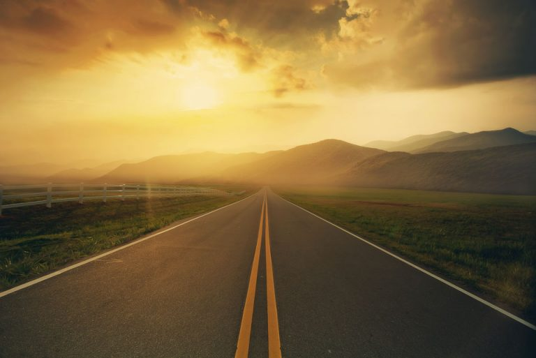 Road leading into mountains with sunset