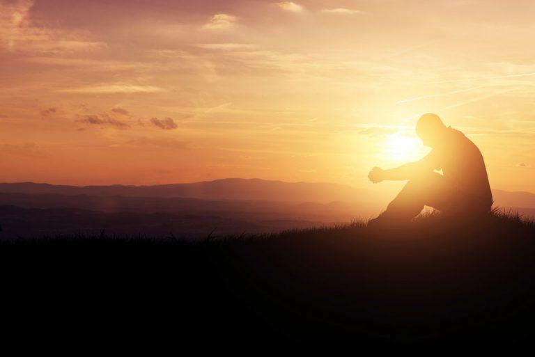 Man sitting on hill praying