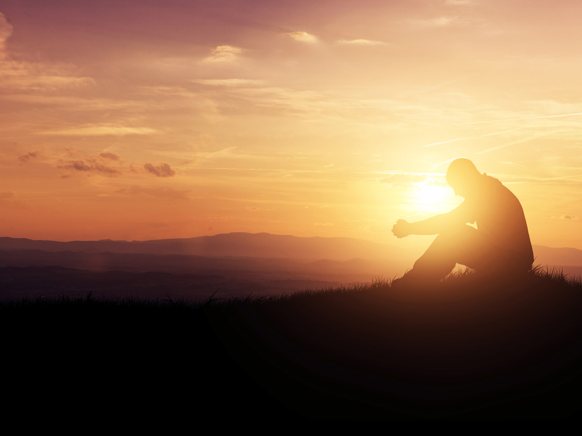 Man sitting on hill praying